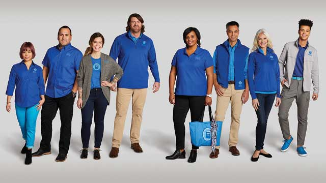 People standing with matching corporate branding apparel.